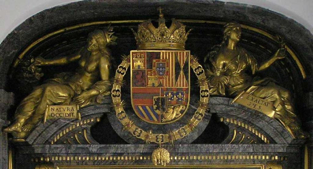 """Десюдепорт в завершии портала, ведущего в Королевскую усыпальницу. В центре - герб Габсбургского дома, корона и цепь высшего рыцарского ордена """"Золотого руна""""... Богатый декор выполнен при Филиппе III - сыне Филиппа II."""